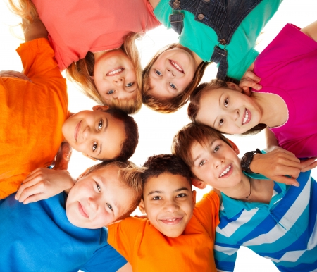 youth group: Circle of smiling positive kids looking down - diversity group of boys and girls
