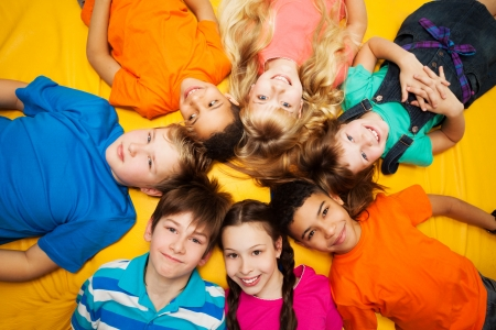Group of happy kids laying in circle - diversity looking Caucasian and black boys and girls smilng photo