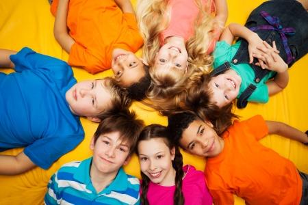 girotondo bambini: Gruppo di bambini felici posa in cerchio - diversit� cercando ragazzi e ragazze caucasiche e nero smilng