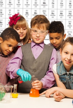 Group of diversity kids boys and girls conductive experiments with periodic table on background photo