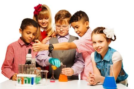 experimento: Grupo de cinco ni�os la diversidad de los ni�os y las ni�as rubias y morena con tubos de ensayo y microscopios y matraces en clase de qu�mica, aislado en blanco