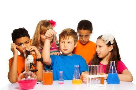 Zespół pięciu dzieci eksperymentujących na lekcji chemii z probówki, płyny i pojemniki na białym