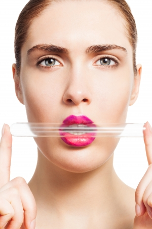 test glass: Portrait of woman holding test tube with her lips isolated on white showing beauty research and development concept Stock Photo