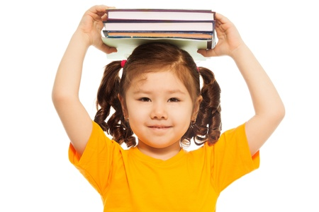 Closeup of happy little Asian girl with ponytails holding pile of books on top of her head  and smile, standing isolated on white photo