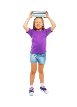 full height: Happy smiling 6 years old girl  full height portrait isolated on white holding books on top of her head Stock Photo