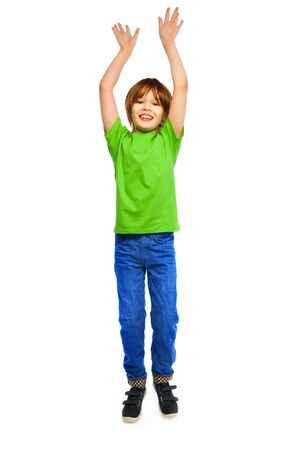 Happy Caucasian boy in green shirt jumping, full height portrait, isolated on white photo