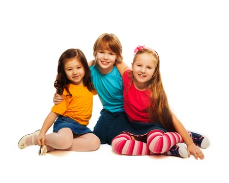 6 7: Group of three 6,7,8 yeas old kids, two girls and boy together, diversity looking happy, laughing, hugging, sitting isolated on white Stock Photo