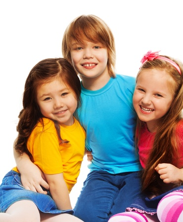 kids hugging: Closeup of a group of three kids, two girls and boy together, diversity looking happy, laughing, hugging, sitting isolated on white