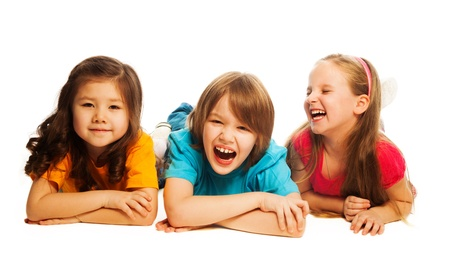6 years: Three happy kids laying on the floor in a line together smiling and laughing, isolated on white