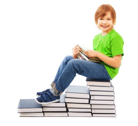 Happy Caucasian 9 years old boy in green shirt sitting on stairs made of stack of books, holding stack of textbooks, isolated on white photo