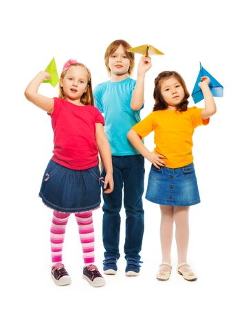 Three little kids standing with colorful paper plane, boy and girl, Caucasian and Asian, isolated on white photo