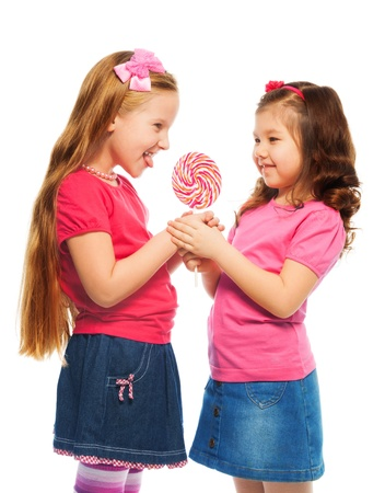 Two girls standing and holding lollipop together isolated on white photo