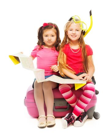 six girl: Two cute little exited girls sitting on suitcase with map preparing to travel wearing snorkel and mask, isolated on white