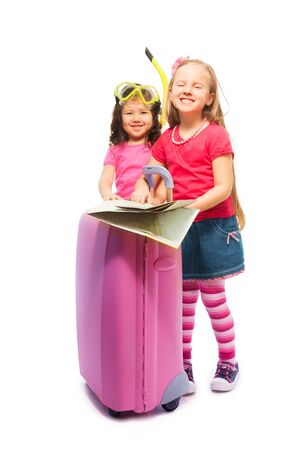 Two cute little exited girls standing with suitcase with map preparing to travel deciding destinations, wearing snorkel and mask, isolated on white Stock Photo - 18394922