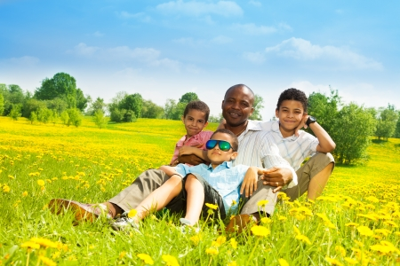 Happy father with his sons sitting on the lawn in the park on sunny day Stock Photo