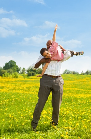 african family: Black father playing with little boy holding him in airplane pose in the park Stock Photo