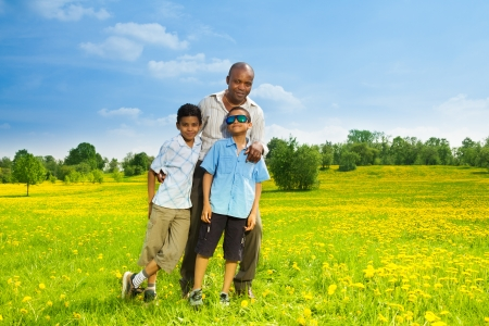 Happy black father with his sons standing on the lawn in the park on sunny day photo