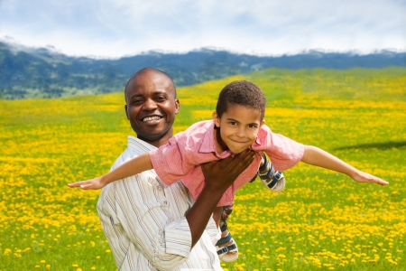 father and child: Black father playing with little boy holding him in airplane pose in spring yellow dandelion field Stock Photo