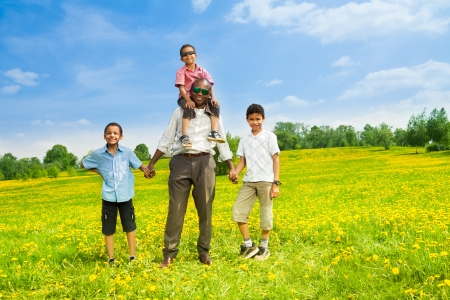Black African man with boys standing together on the field in the spring park photo