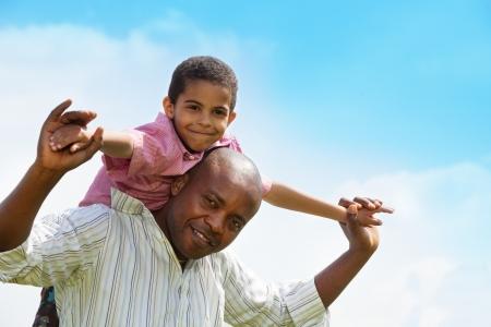 famille africaine: Close-up portrait p�re afro-am�ricain et le soleil jouant ensemble Banque d'images