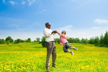 Happy black father with his son rotating his boy on the field with yellow dandelions in the park