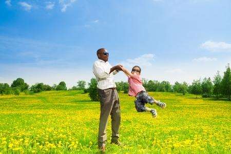 afroamericanas: Padre negro feliz con su hijo girando a su hijo en el campo con dientes de león amarillos en el parque Foto de archivo