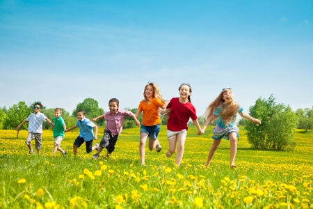 kids activities: Group of seven running in the park kids, boys and girls, black and Caucasian Stock Photo