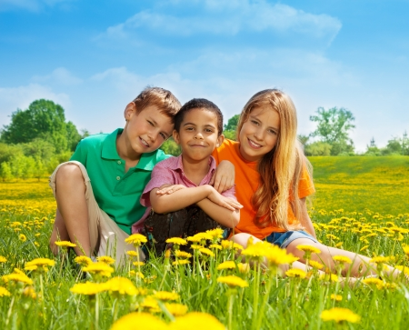 Three happy kids sitting in the dandelion field in the sunny early summer day photo