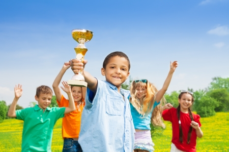 Portrait of black happy smiling little boy holding prize cup with his team on background photo