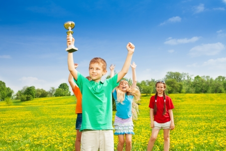 lifted hands: Portrait of happy little boy holding prize in lifted hands cup with his team cheering on background
