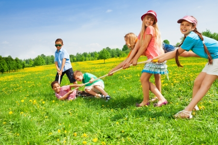 Team of boys against girls pulling the rope in dandelion