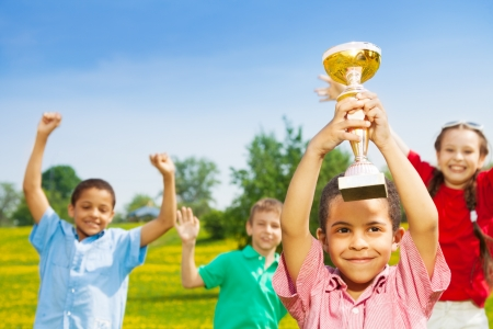 Close shoot of black happy smiling little boy holding prize cup with group of boys and girls on background