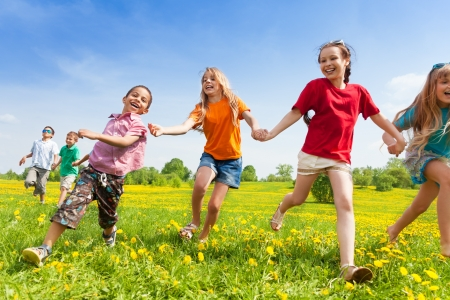 多様性の子供、男の子と女の子の黄色い花のスプリング フィールドで実行しているを探しています 写真素材