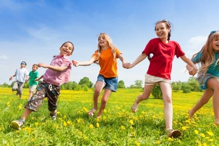 Diversiteit kijken kinderen, jongens en meisjes die in de gele bloemen lente veld Stockfoto