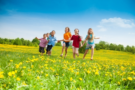 Group of happy kids running in the yellow flowers field summer day