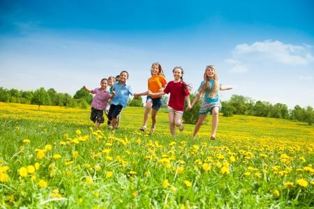 ni�os felices: Grupo de ni�os felices corriendo en el campo de flores amarillas d�a de verano