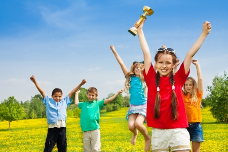 Group of happy kids of winner team with leader holding prize award cup Stock Photo