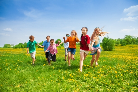 children playing outside: Large group of kids running in the dandelion spring field
