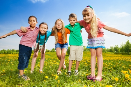 Five happy kids hugging together standing in the dandelion field