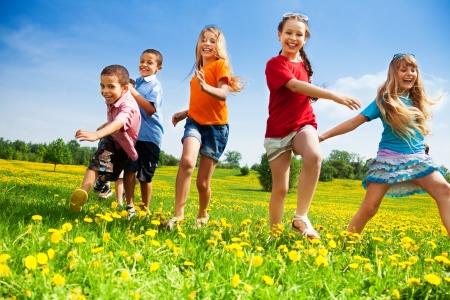 Vijf gelukkige diversiteit zoek kinderen lopen in het park Stockfoto