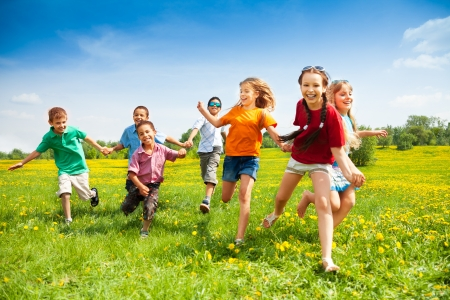 kids playing outside: Large group of children running in the dandelion spring field