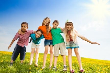 ni�o corriendo: Cinco ni�os felices, ni�os y ni�as abrazando juntos de pie en el campo de flor amarilla Foto de archivo