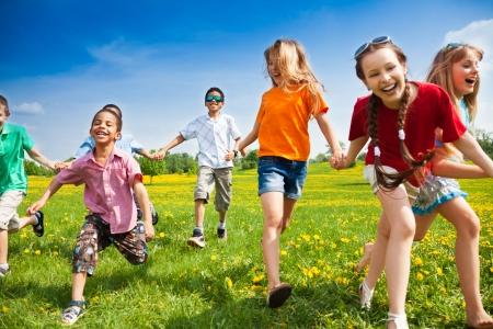 タンポポのスプリング フィールドで走っている子供の大規模なグループ