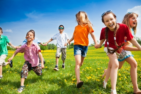happy children: Large group of children running in the dandelion spring field
