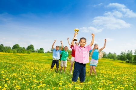 lifted hands: Group of kids with lifted hands and with prize cup