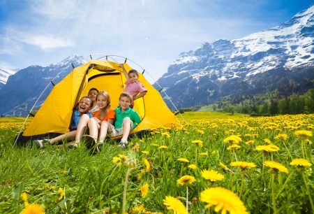 Group of kids, boys and girls sitting together in the tent in dandelion field photo