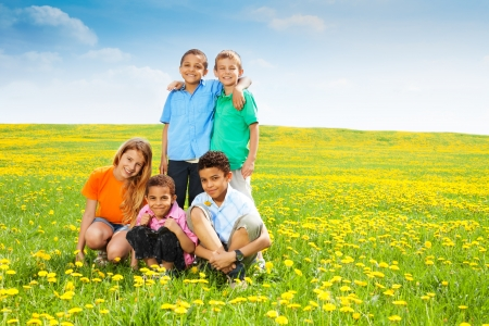 Five happy diversity looking kids, boys and girls in the clean dandelion field photo