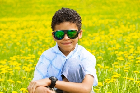 Happy little black boy in sunglasses sitting in the dandelion field photo