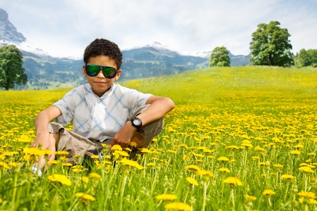 Happy little black boy in sunglasses sitting in the dandelion field with mountains on background photo