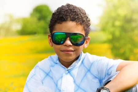 Close portrait of happy 10 years old black boy in sunglasses in the park photo